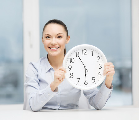 career timing: business, office, school and education concept - attractive businesswoman showing clock