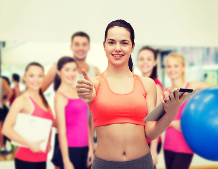 sport, exercise, technology, internet and healthcare - sporty woman with tablet pc computer showing thumbs up photo