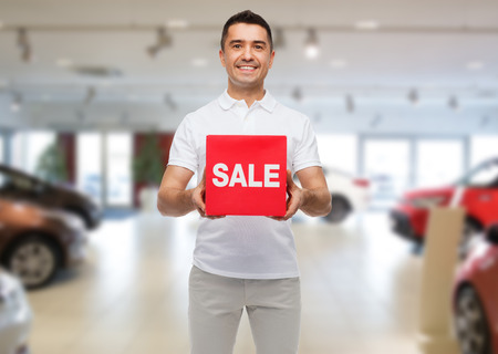 consumerism: shopping, consumerism, discount and people concept - smiling man with red sale sigh over auto show background