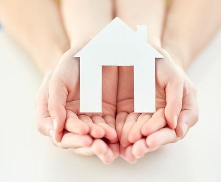 viviendas: la gente, la caridad, la familia y el hogar concepto - cerca de la mujer y la ni�a con la casa de papel recortado en manos ahuecadas