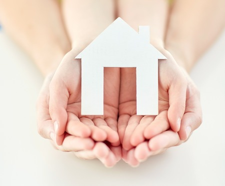 people, charity, family and home concept - close up of woman and girl holding paper house cutout in cupped hands Stockfoto