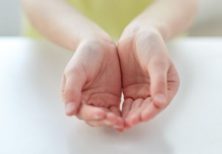 people, charity, childhood and advertisement concept - close up of child cupped hands at home Reklamní fotografie