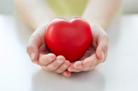 hearts and hands: people, love, charity and family concept - close up of child hands holding red heart shape at home