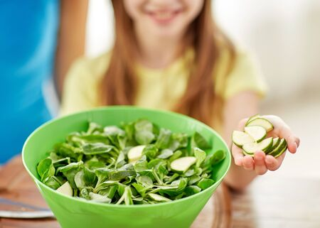 food, family, cooking and people concept - close up of happy girl making dinner and adding cucumber slices to green salad bowl in kitchen Stock Photo