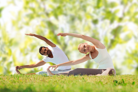 outdoor sports: fitness, sport, yoga and people concept - happy couple stretching on mats over green tree leaves background