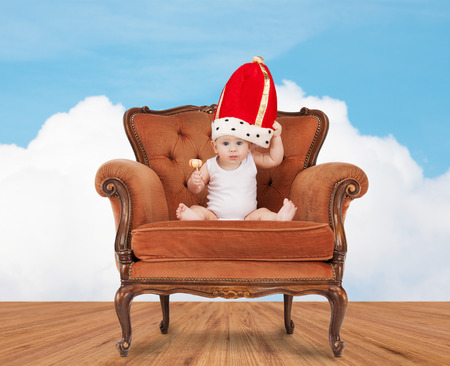 people, childhood and royalty concept - happy baby boy in royal hat with lollipop sitting on chair over blue sky and cloud background photo