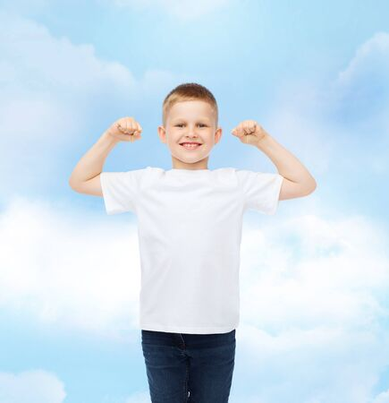advertising, dream, people and childhood concept - smiling little boy in white blank t-shirt with raised hands over cloudy sky background photo