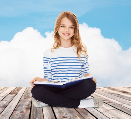 cute little girls: education, childhood, people and school concept - little student girl studying and reading book over blue sky and cloud background