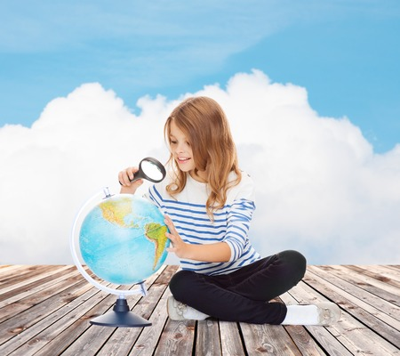 schoolkid search: la educaci�n, los viajes, la infancia, la geograf�a y la escuela concepto - Ni�a feliz estudiante que mira el globo con la lupa sobre el cielo azul y nubes de fondo