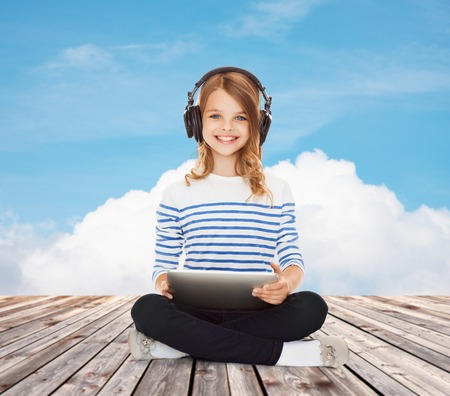 music, technology, people and childhood concept - happy girl with headphones and tablet pc computer over blue sky and cloud background photo