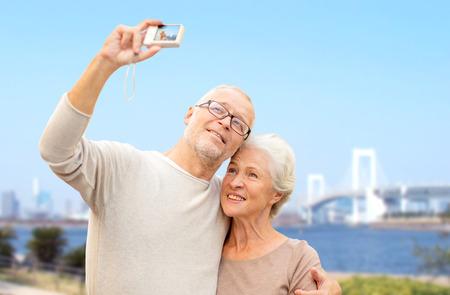 jubilados: edad, turismo, viajes, tecnolog�a y concepto de la gente - pareja senior con c�mara que toma Autofoto en calle de la ciudad por el puente del arco iris en el fondo del r�o y