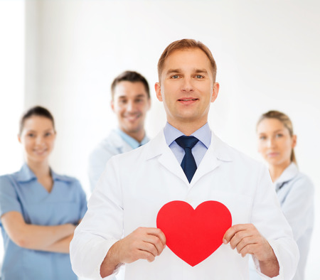 medics: medicine, profession, charity and healthcare concept - smiling male doctor with red heart over group of medics