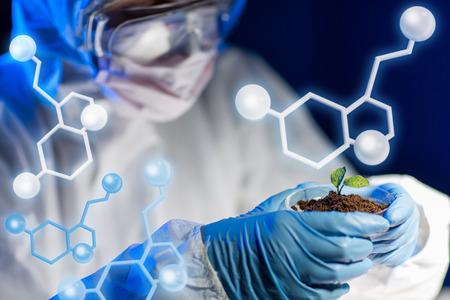 biologia: ciencia, biolog�a, ecolog�a, la investigaci�n y el concepto de la gente - cerca de joven cient�fico la celebraci�n placa de Petri con la planta y muestra de suelo en laboratorio bio sobre la estructura molecular Foto de archivo