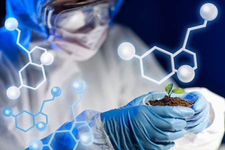 molecular structure: science, biology, ecology, research and people concept - close up of young scientist holding petri dish with plant and soil sample in bio laboratory over molecular structure