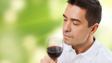 degustating: profession, drinks, leisure and people concept - happy man drinking and smelling red wine from glass over green background