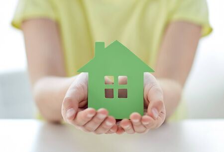 hands cupped: people, charity, family and home concept - close up of happy girl holding green paper house cutout in cupped hands