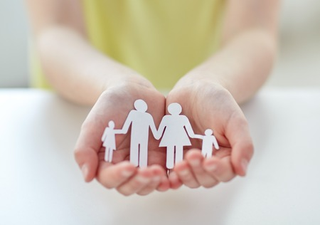 kids holding hands: people, charity and care concept - close up of child hands holding paper family cutout at home