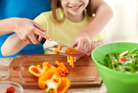 food, family, cooking and people concept - close up of happy girl and mother making salad for dinner and chopping paprika on cutting board with knife in kitchen