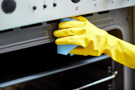 cleaning kitchen: people, housework and housekeeping concept - close up of woman hand in protective glove with rag cleaning oven at home kitchen