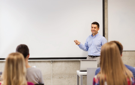 college class: education, high school, technology and people concept - smiling teacher standing with remote control, laptop computer in front of white board and students in classroom
