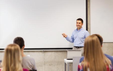 onderwijs, middelbare school, technologie en mensen concept - lachende leraar staan met afstandsbediening, laptop computer in de voorkant van de witte boord en studenten in de klas Stockfoto