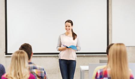 salle de classe: l'éducation, l'école secondaire, le travail d'équipe et les gens le concept - jeune fille souriante étudiante avec le cahier debout devant des étudiants en classe