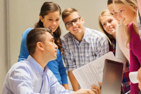 clase media: la educación, la escuela secundaria, la tecnología y concepto de la gente - grupo de estudiantes sonrientes y profesor de papeles, ordenador portátil en el aula Foto de archivo