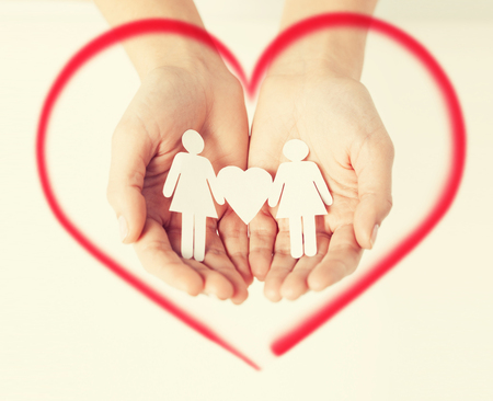 love, family and happiness concept - womans hands showing two paper women with heart shape photo