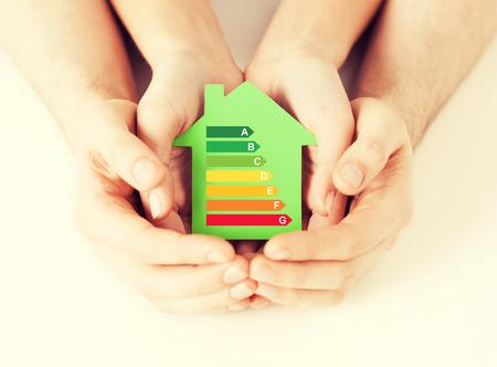ahorro de energía, bienes raíces y el concepto de hogar - Detalle de la pareja tomados de la mano casa de papel verde con calificación de eficiencia energética Foto de archivo