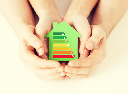alternative energy: energy saving, real estate and family home concept - closeup of couple hands holding green paper house with energy efficiency rating