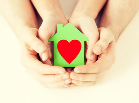 hands holding house: charity, real estate and family home concept - closeup picture of male and female hands holding green paper house with red heart
