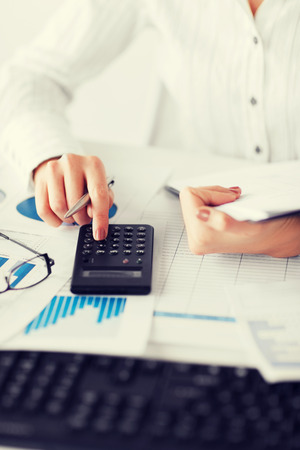 bookkeeping: business, office, school and education concept - woman hand with calculator and papers
