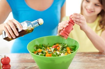ni�os sanos: alimentos, la alimentaci�n saludable, la familia y las personas concepto - cerca de la chica feliz y madre que cocina la ensalada para la cena y la adici�n de especias en la cocina