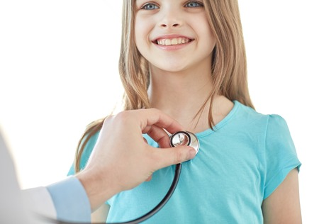 healthcare, medical exam, people, children and medicine concept - close up of happy girl and doctor hand with stethoscope listening to heartbeat Stock Photo