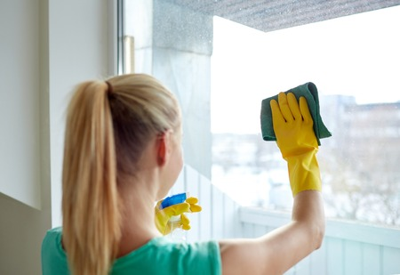 people, housework and housekeeping concept - happy woman in gloves cleaning window with rag and cleanser spray at home Stock Photo