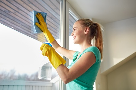 cleanser: people, housework and housekeeping concept - happy woman in gloves cleaning window with rag and cleanser spray at home Stock Photo