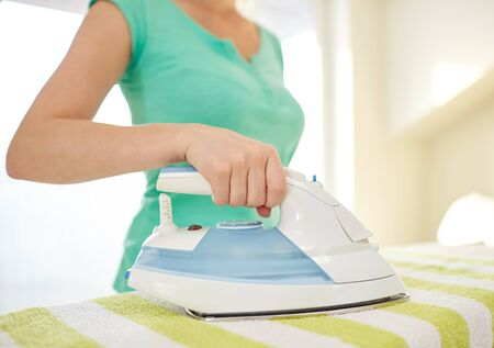 iron: people, housework, laundry and housekeeping concept - close up of happy woman with iron and ironing board at home