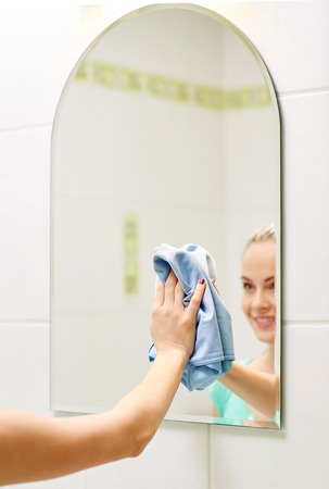 mirror: people, housework and housekeeping concept - close up of happy woman cleaning mirror with rag at home