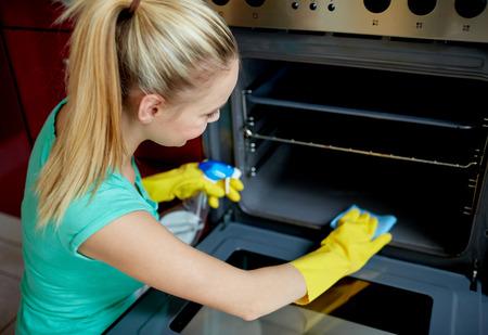 clean home: mensen, huishoudelijk werk en het huishouden concept - tevreden vrouw met fles spray reinigingsmiddel schoonmaken oven thuis keuken