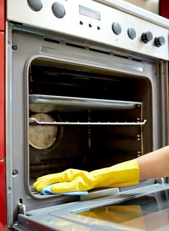 domestic: las personas, el trabajo doméstico y de limpieza concepto - cerca de la mano de la mujer en el guante protector con horno de limpieza de trapo en la cocina de casa