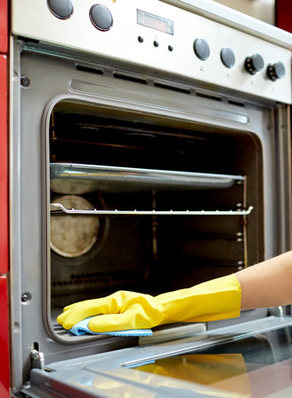 oven: people, housework and housekeeping concept - close up of woman hand in protective glove with rag cleaning oven at home kitchen