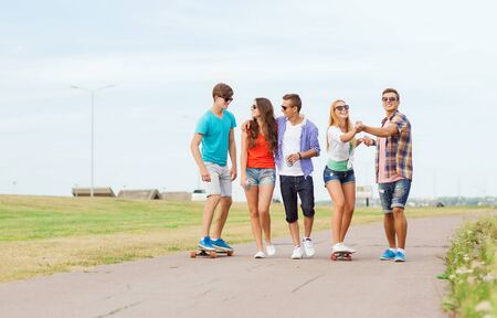 group of teenagers: holidays, vacation, love and friendship concept - group of smiling teenagers walking and riding on skateboards outdoors
