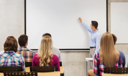 education, high school, teamwork and people concept - smiling teacher standing in front of students and writing something on white board in classroom Foto de archivo