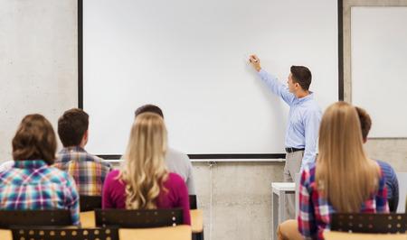 clase media: la educación, la escuela secundaria, el trabajo en equipo y la gente concepto - profesor sonriente de pie delante de los estudiantes y escribir algo en la pizarra en el aula Foto de archivo
