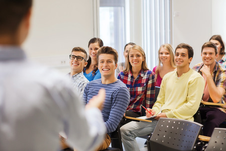 teach: education, high school, teamwork and people concept - group of smiling students with notebooks and teacher in classroom
