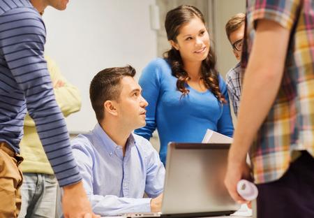 maestro: la educaci�n, la escuela secundaria, la tecnolog�a y concepto de la gente - grupo de estudiantes sonrientes y profesor de papeles, ordenador port�til en el aula Foto de archivo