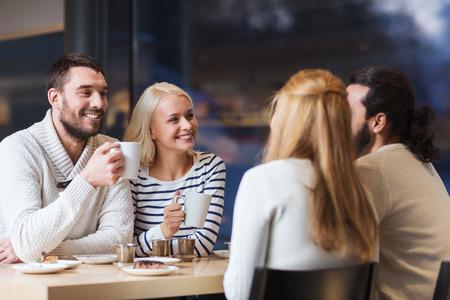 Persone, il tempo libero, la comunicazione, mangiando e bevendo concept - amici felici riunioni e bere tè o caffè al bar Archivio Fotografico - 37682720