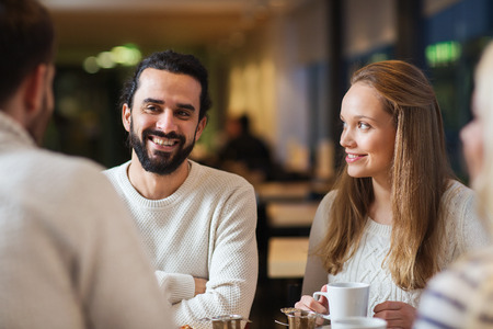 latin people: people, leisure, communication, eating and drinking concept - happy friends meeting and drinking tea or coffee at cafe