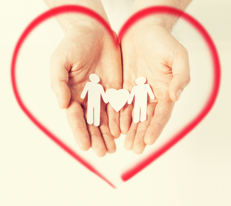 family, love and happiness concept - mans hands showing two paper men with heart shape photo