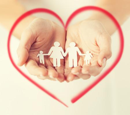 el amor, la familia y la felicidad concepto - cerca de manos de mujeres que muestran hombre de familia de papel Foto de archivo